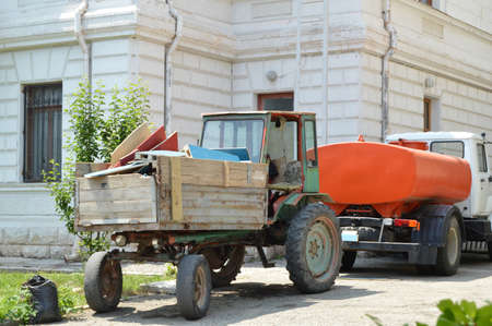 Old tractor with garbage in the back is near the watering machine, cleaning equipment for cleanliness in parks on a Sunny summer day.