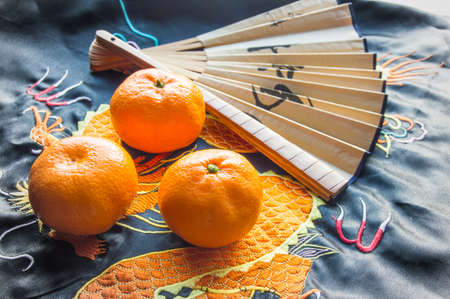 Chinese new year-traditional pink fan and tangerines on silk fabric, background with embroidered dragon