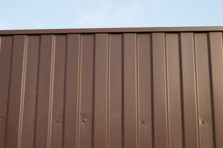 Modern aluminum fence of corrugated panel corrugated metal siding brown.