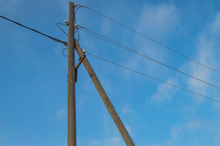 Wooden old 0.4 kV power line support with wires and insulators on blue sky background.