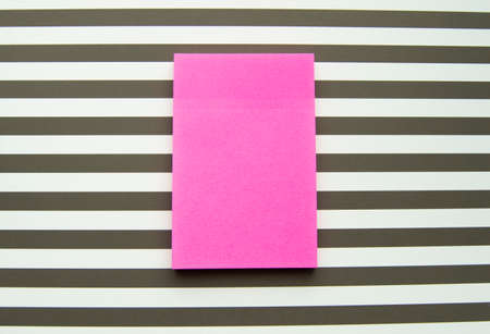 Red message sticker on black and white striped background, business objects. 版權商用圖片