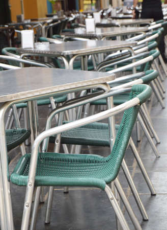Open empty street cafe, tables and chairs with metal frame and wicker furniture, selective focus and close-up