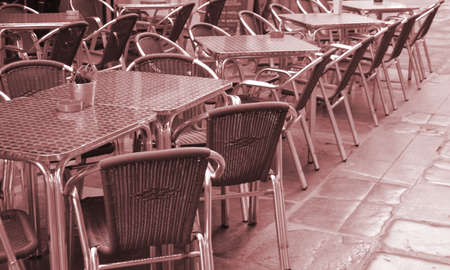 Open empty street cafe, tables and chairs with metal frame and wicker furniture, selective focus and close-up.