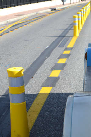 Yellow striped poles along the road divide the direction of traffic, the concept of road safety.
