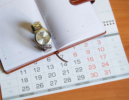 Workplace for men businessman with a clock, calendar and organizer on a wooden table.