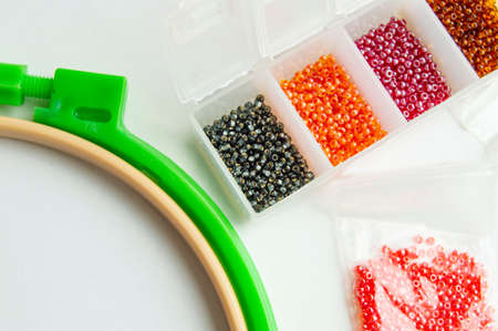 Flat lay Accessories for needlework and embroidery, hoops and beads on white background.