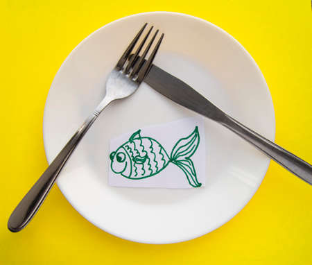 The celebration of April fool's Day, a Plate with a fork and knife and a paper fish on a yellow colored background. Humor.