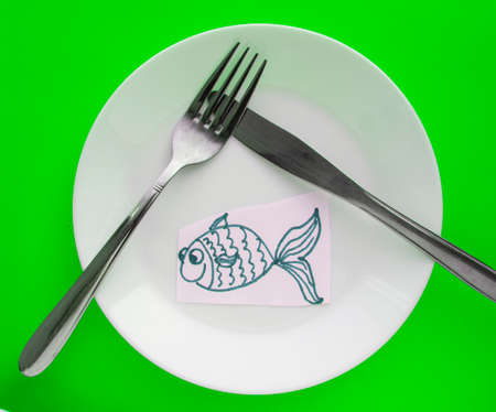 The celebration of April fool's Day, a Plate with a fork and knife and a paper fish on a green background. Humor.
