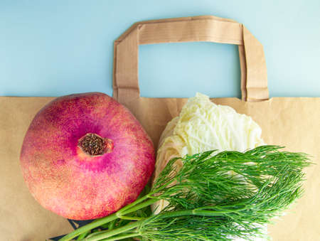 Flat lay, Healthy fruits and vegetables for proper nutrition on top of a paper bag, the concept of abandoning plastic bags and shopping at a diet for weight loss. The view from the top.