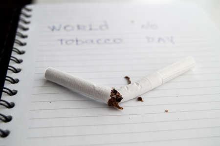 World no tobacco day, no Smoking day. Broken cigarette on business notebook, minimalism.