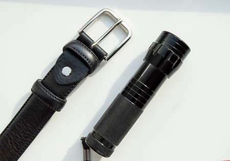 Mens accessories black leather strap and flashlight isolated on white background.