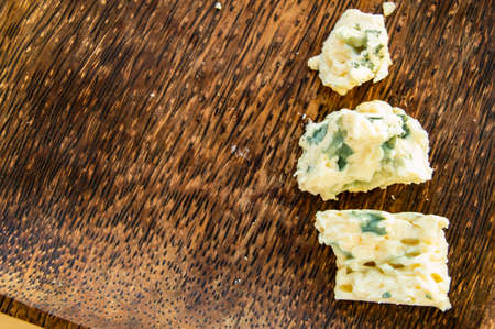 Three broken pieces of blue cheese on a dark wooden plate and minimalism, top view, copy space. Imagens