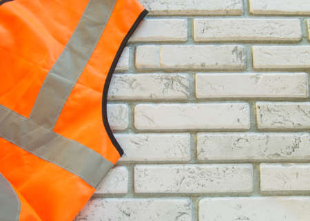 Construction orange vest with reflective stripes for safety on white brick background, copy space