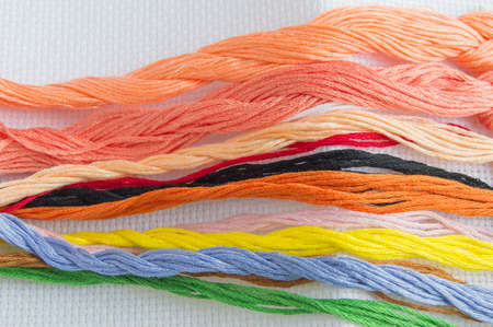 Bright colorful thread for embroidery thread on canvas. Handmade accessories on white background. Place for text, top view.