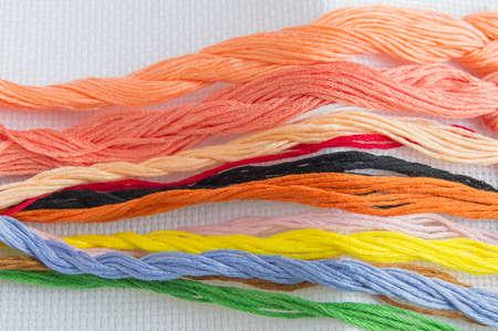 Filo colorato brillante per filo da ricamo su tela. Accessori fatti a mano su sfondo bianco. Posto per il testo, vista dall'alto. Archivio Fotografico