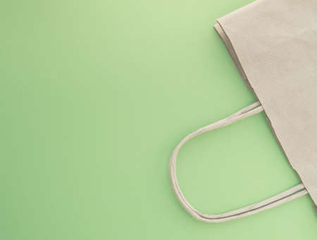 Concept of zero waste, reusable paper bag for shopping, free plastic, green background, top view.