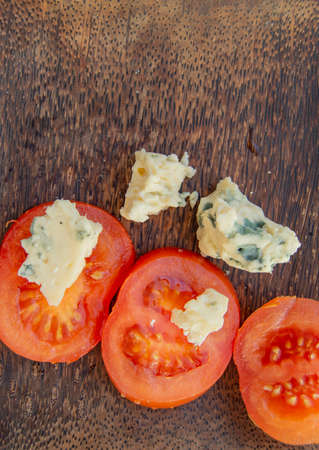 Italian culinary ingredients sliced tomatoes and cheese with mold on a dark rustic wooden plate, top view