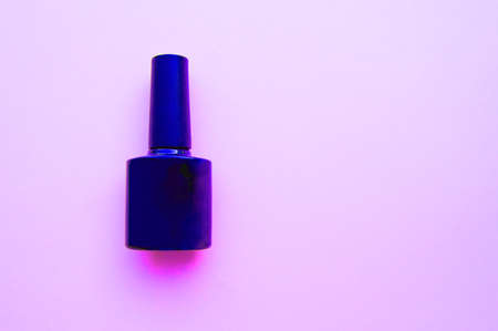 One bottle of nail Polish with neon light on pink background, place for promotional test, layout for beauty blog. 版權商用圖片