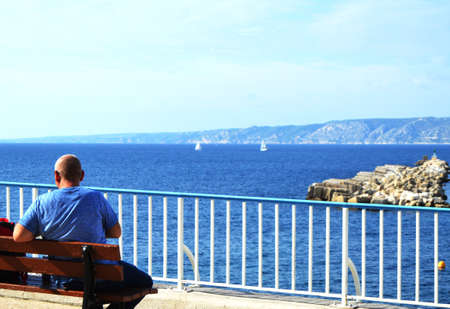 A young man traveler sitting on a bench on the Mediterranean coast on the promenade of Marseille. Back view of the beautiful sea panorama and sailboats, a COPY of the SPACE. Stock Photo