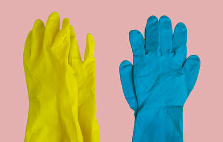 Top view of yellow and blue rubber protective gloves on pink table for spring or daily cleaning. The concept of a commercial cleaning company Фото со стока