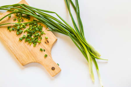 Fresh green onion feathers and cut into pieces on a wooden chopping Board. Top view, flat lay, copying space isolated on white background. Banco de Imagens - 122116019