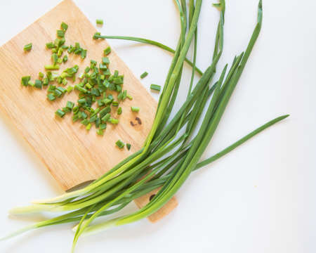 Fresh green onion feathers and cut into pieces on a wooden chopping Board. Top view, flat lay, copying space isolated on white background.