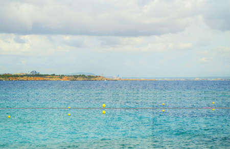 Sun's rays Shine through the clouds over the turquoise sea on the beach of Palma de Mallorca, a tranquil scene with a copy of the space.