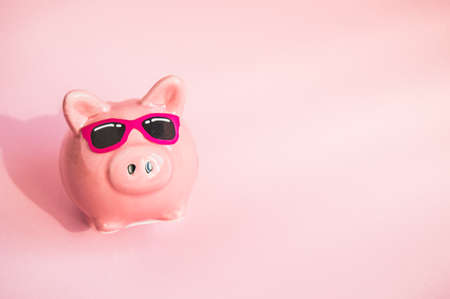 Funny piggy Bank in sunglasses on pink background, sunlight, copy space, money saving concept for summer vacation.