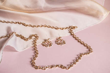 Luxury gold jewelry chain and earrings on pink background with silk, copy space, selective focus.