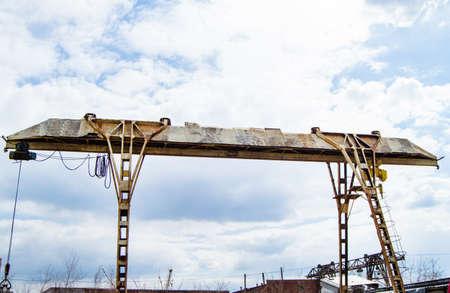 Old rusty gantry crane on blue sky background.