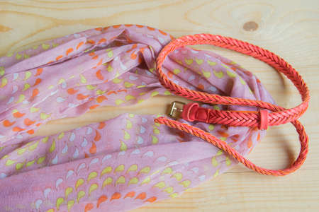 Fashionable pink accessories on wooden background - scarf, belt.