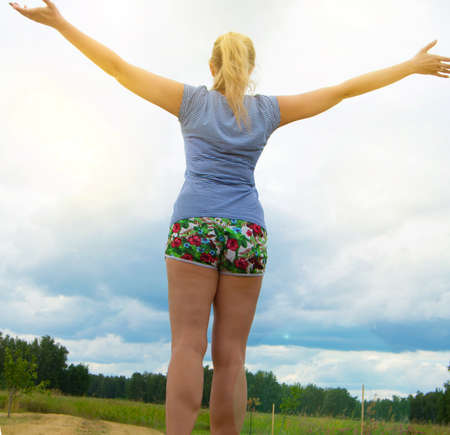 Happy young blonde wearing shorts and a t-shirt stands on the road against the sky with her arms outstretched, illuminated by sunlight on a summer day. Фото со стока