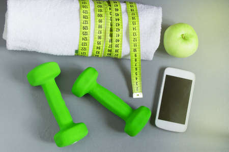 Fitness concept, dumbbell, mobile and a towel and measuring tape, top view. 免版税图像