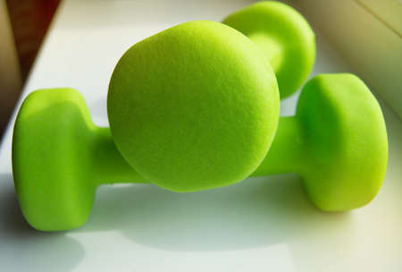 Concept of fitness, healthy lifestyle-two green dumbbells for sports, sunlight.