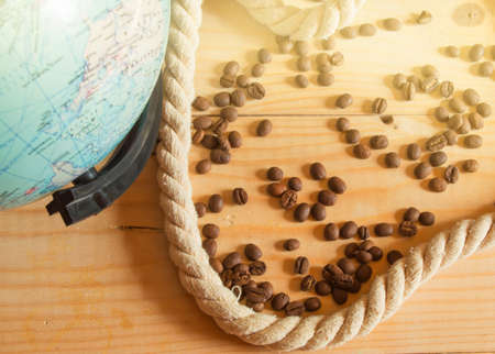 Happy OPENING day of Columbus. A globe, a rope, coffee beans on a wooden Board, SOLAR LIGHT. Banco de Imagens
