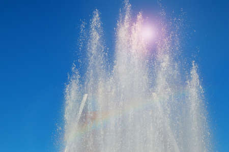 Fountain in the Park with water jets and splashes against the blue sky on a Sunny summer day. 免版税图像