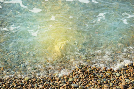 Sea wave on the shore of a pebble beach, water, foam, background.