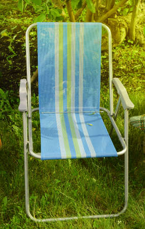 Folding chair camping is located in the garden on the grass on a Sunny summer day.
