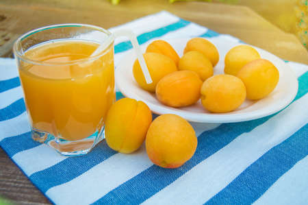 Summer drink and fruit-fresh apricot juice in a glass glass Cup with a straw and ripe apricots on a napkin, outdoors on a Sunny day. Reklamní fotografie
