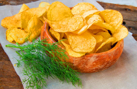 Crispy potato chips with dill in a wooden bowl on linen napkin.