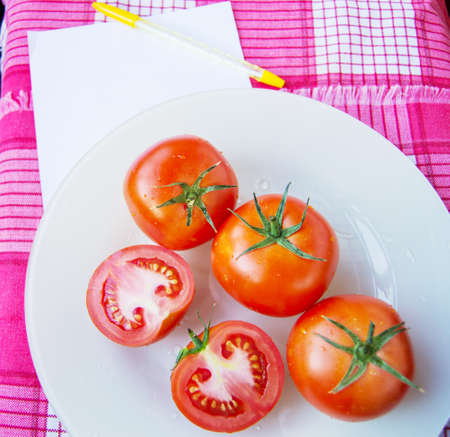 Fresh ripe red tomatoes and sliced tomatoes with water drops and a green peduncle on a white plate, next to a sheet of Notepad for writing and controlling the diet - top view