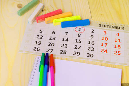 Back to school, calendar, colored chalk on wooden background. Imagens