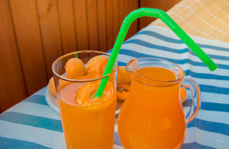Summer drink - apricot juice in a glass jug and in a glass glass Cup with straw and straw on a striped napkin on a Sunny summer day.