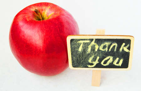 Apple with Thank you inscription on a wooden Board black background 写真素材