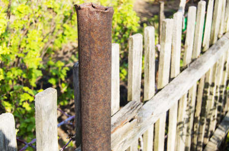 Old rusty metal pipe, pillar, and wooden fence at the garden in spring, summer.