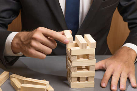 Businessman in business suit building a tower of wooden blocks, strategy and planning in business. Banque d'images - 122978416