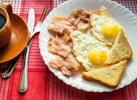 Delicious Breakfast - a Cup of coffee, a plate of fried eggs, bacon and toast, next to the Cutlery on red checkered napkin. Imagens
