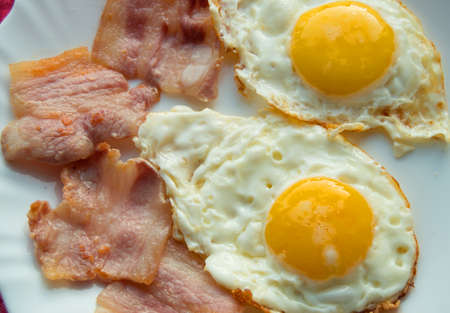 Delicious Breakfast - white plate of fried eggs, bacon. Stock Photo