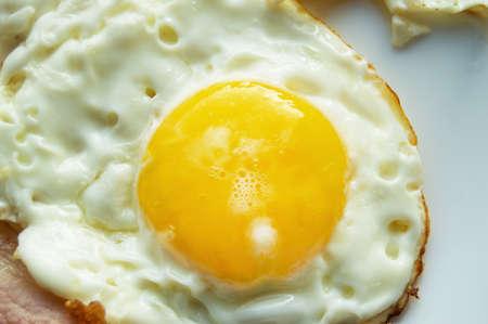 Delicioso desayuno - plato blanco con huevo frito, primer plano.