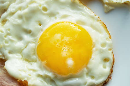 Delicious Breakfast - white plate with fried egg, close-up.